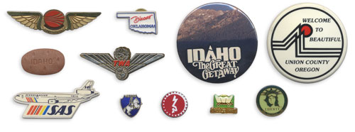 TWA wings, SAS wings, an Idaho potato button, Discover Oklahoma!, Idaho The Great Getaway, Welcome to Beautiful Union County, Vienna pin, Berlin Jewish Museum pin, Oregon Trail pin, Statue of Liberty pin