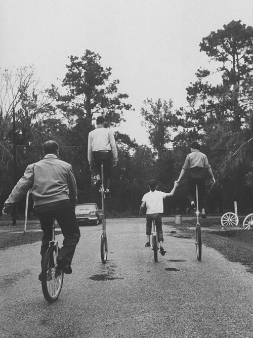 A family of unicyclers, rolling down a path.