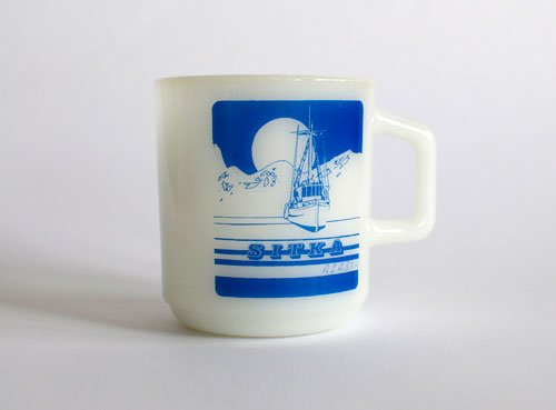 Sitka, Alaska mug - scene of a boat, some mountains, and either a sun or a moon.