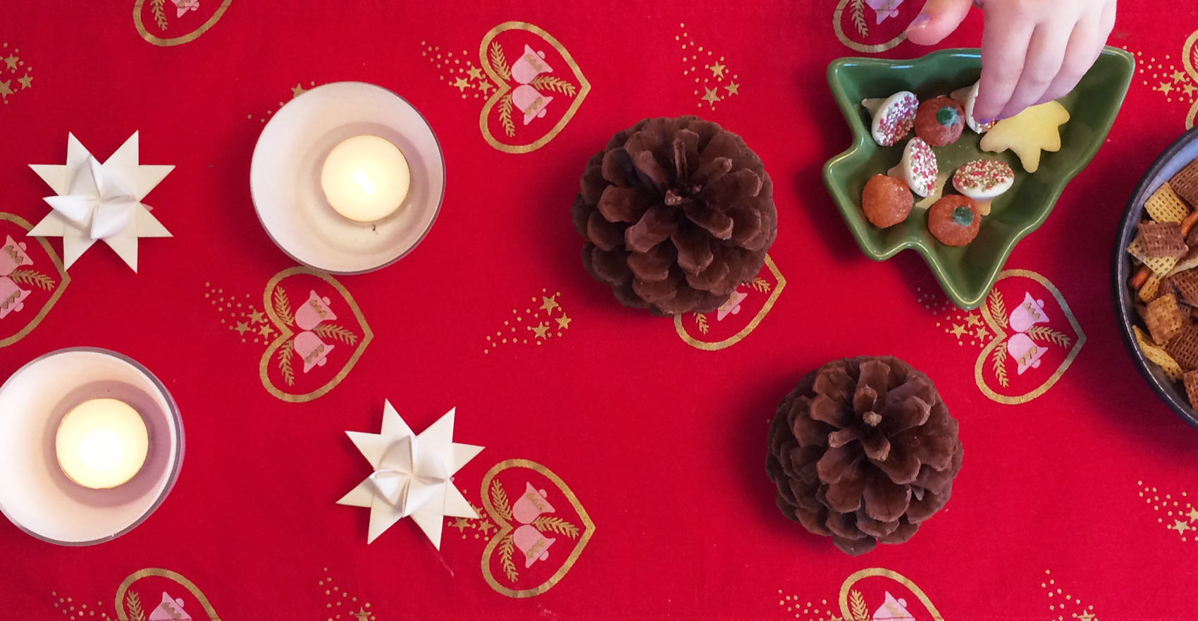 red table cloth with Danish christmas start and pine cone decorations. And chex mix.