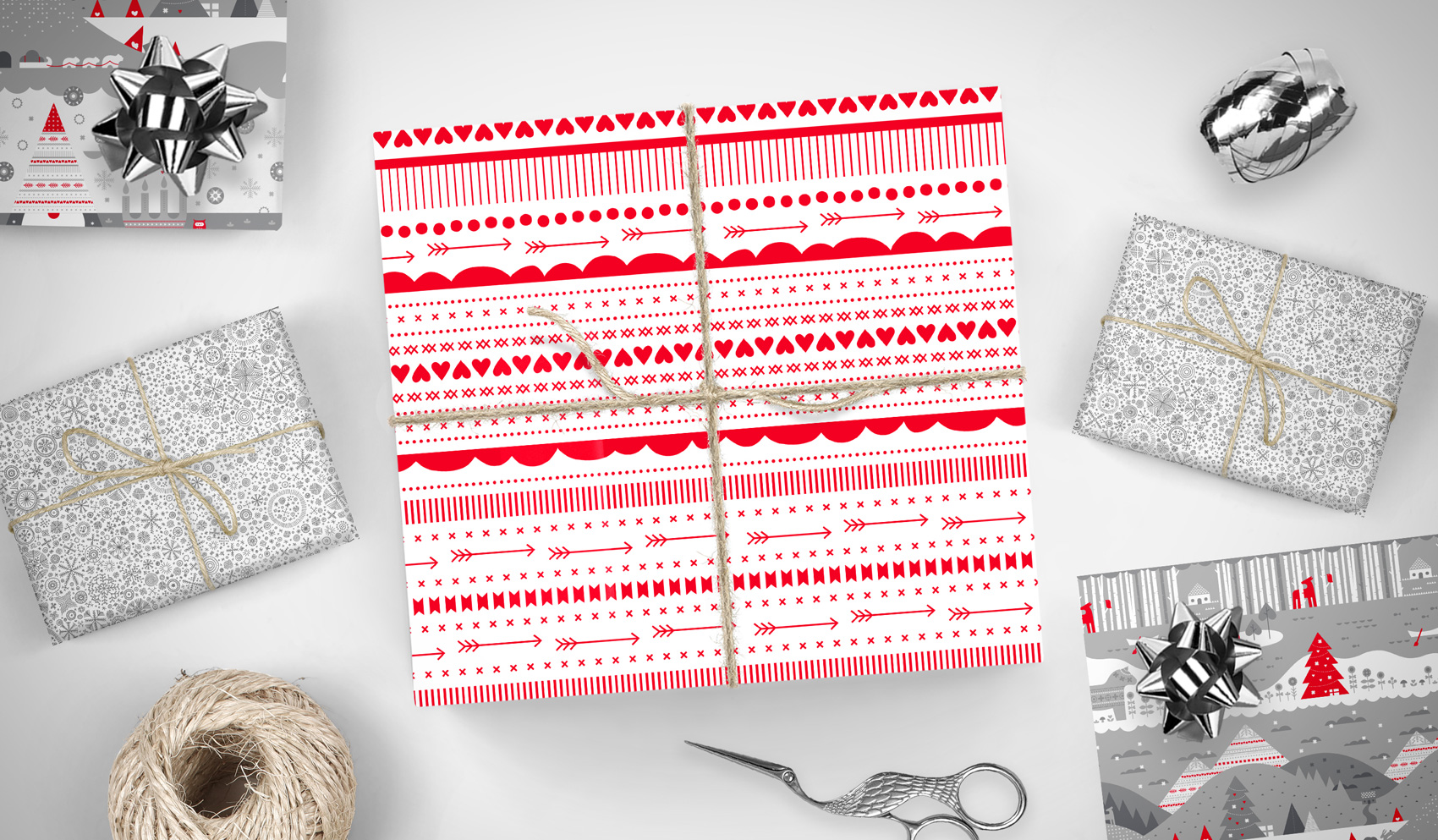 Gift wrap patterns on presents: red ribbons, silver snowflakes and tonal gray gnome villages.